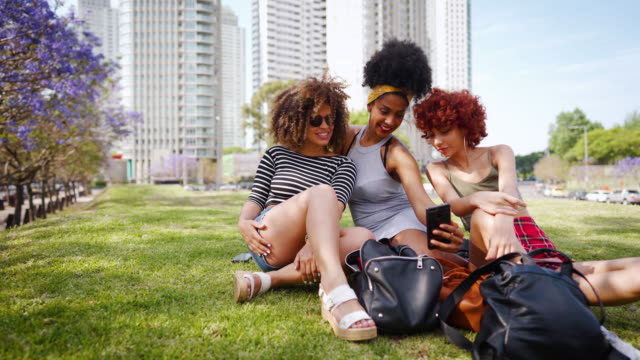 female friends taking selfie while sitting on grass at public park in buenos aires - fashionable stock videos & royalty-free footage