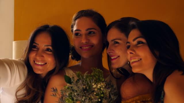 cu female friends taking selfie with bride in hotel room before wedding ceremony - 若い女性点の映像素材/bロール