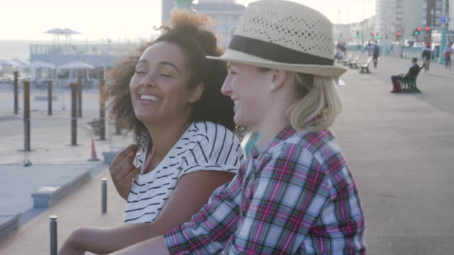 female friends talking and laughing standing on beach promenade. - carefree stock videos and b-roll footage