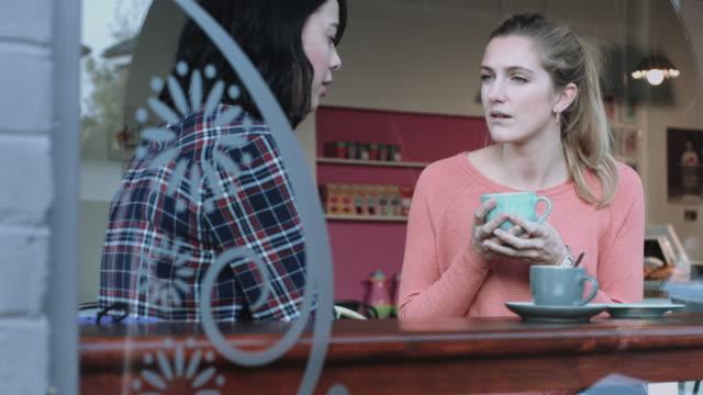 Female friends talking in coffee shop