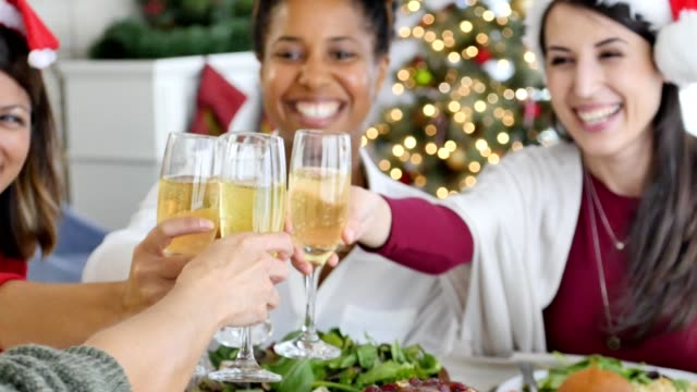Female friends toast champagne during Christmas dinner
