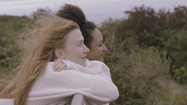 female friends together looking at the view and pointing, wearing sweaters in autumn with moody sky - cool attitude stock videos & royalty-free footage