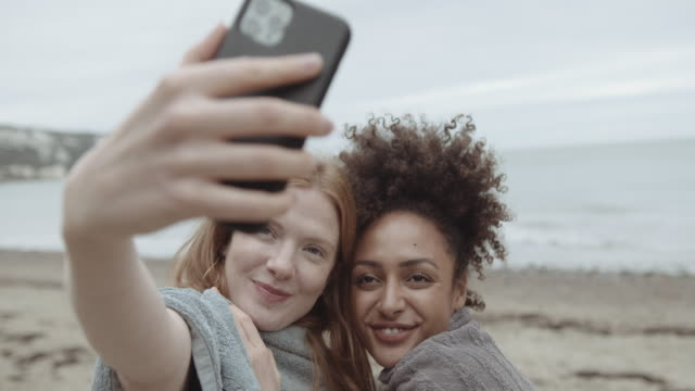 female friends together on beach taking selfie with smart phone outdoors on beach - kent england stock videos & royalty-free footage