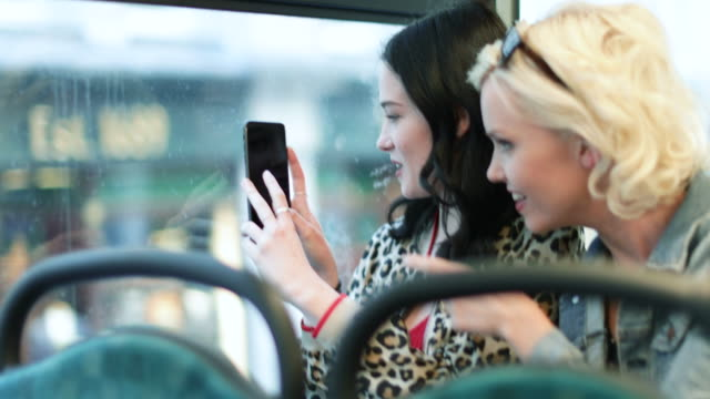 Female friends travelling through London on a bus