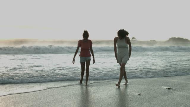 female friends walking at sea shore - 14歳から15歳点の映像素材/bロール