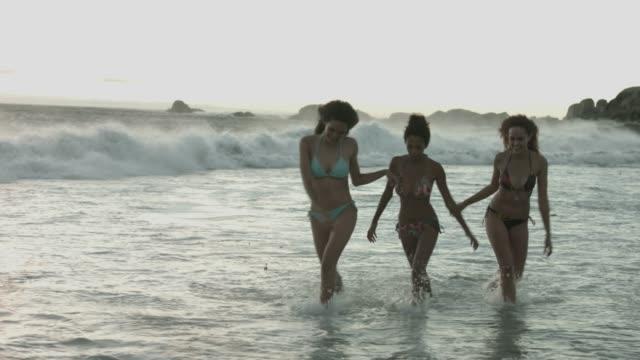 female friends walking in sea during sunset - 14歳から15歳点の映像素材/bロール