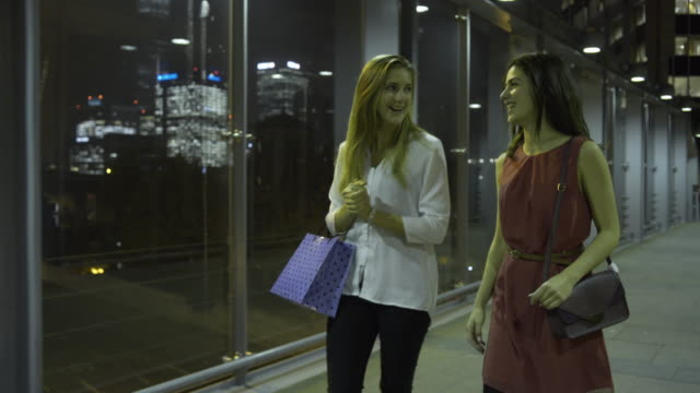 female friends walking with shopping bags in city at night - shopping bag stock videos & royalty-free footage