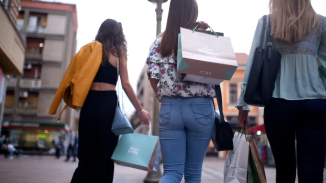 female friends walking with shopping bags - shopping bag stock videos & royalty-free footage