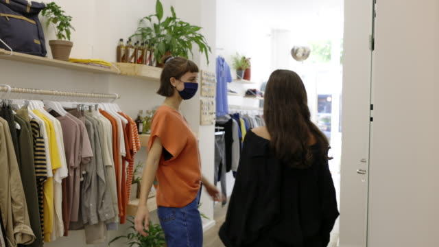 female friends wearing face mask shopping clothes in a store - clothes shop stock videos & royalty-free footage