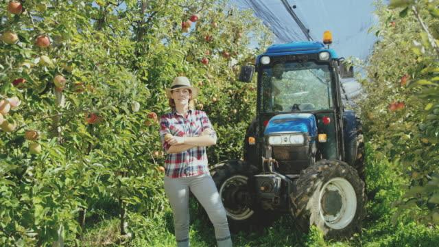stockvideo's en b-roll-footage met ds vrouwelijke fruit boer poseren in appelboomgaard - armen over elkaar