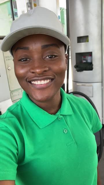 vídeos de stock e filmes b-roll de female gas station attendant doing a video call at work - pov of camera - frentista