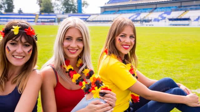 CU female german sport fans at soccer stadium smiling into camera