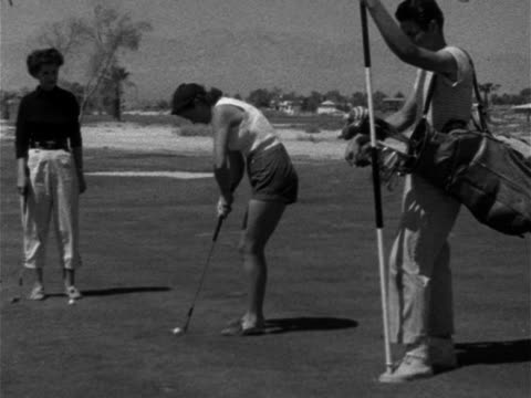 stockvideo's en b-roll-footage met female golfer in shorts putting ball toward hole on 16th green female male caddie standing watching upscale upper class luxury leisure sport relaxing - korte broek
