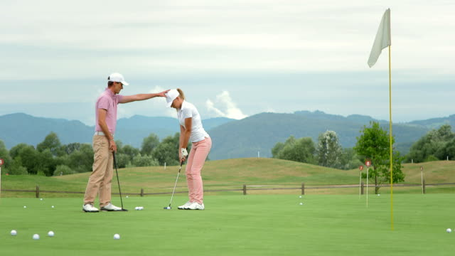 hd dolly: female golfer learning putting position - manager stock videos & royalty-free footage