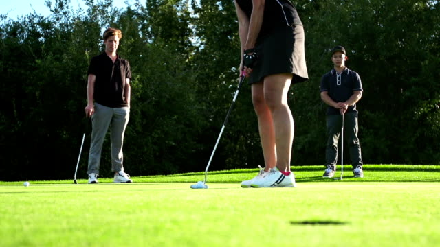 Female golfer makes a putt.