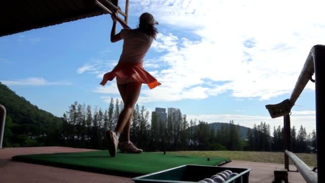 vídeos y material grabado en eventos de stock de slo mo golfer femenino teeing off. - swing de golf