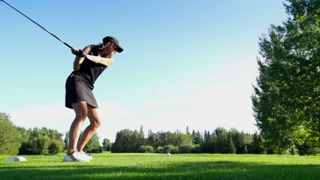 Female golfer tees off.