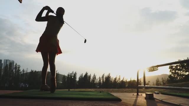 vídeos y material grabado en eventos de stock de golfista femenina con golf swing contra - green de golf