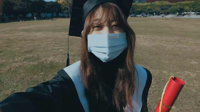 female graduate in cap and gown wearing medical face mask - cap stock videos & royalty-free footage