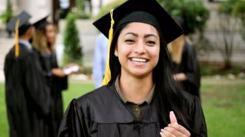 en kvinnlig examen tittar på kameran och ler med spänning - examen bildbanksvideor och videomaterial från bakom kulisserna