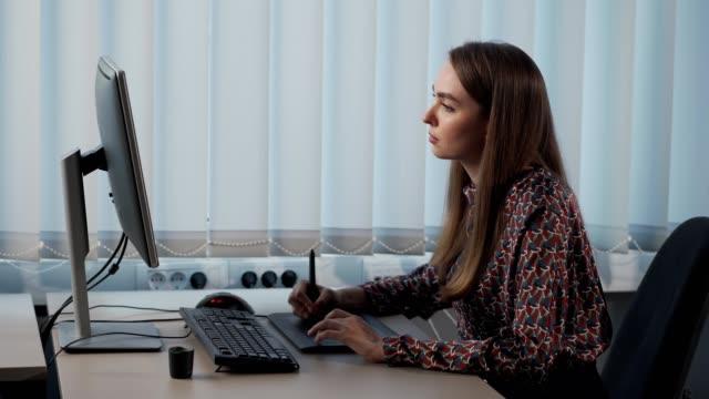graphic designer donna che lavora in ufficio - serio video stock e b–roll