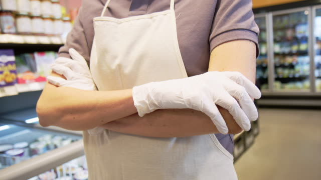 female grocery store employee with hands gloves and apron - glove stock videos & royalty-free footage