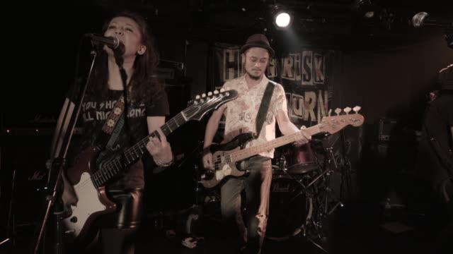 ms female guitarist singing on stage / nakano, tokyo, japan - ギタリスト点の映像素材/bロール