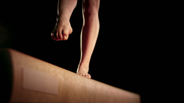 slo mo female gymnast doing a back walkover on the balance beam - gymnastics stock videos & royalty-free footage