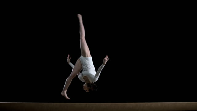 slo mo female gymnast doing a flip on balance beam - acrobatic activity stock videos & royalty-free footage