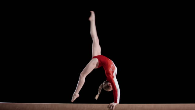 slo mo female gymnast performing a back walkover on the balance beam - gymnastics stock videos & royalty-free footage
