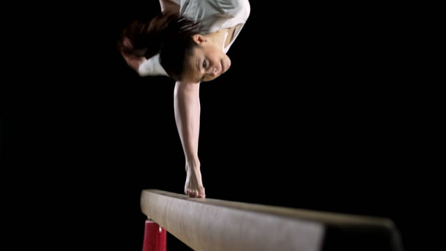 slo mo female gymnast performing a flip on balance beam - gymnastics stock videos & royalty-free footage
