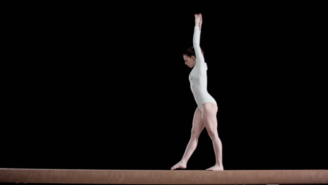 slo mo female gymnast performing a flip on the balance beam - balance stock videos & royalty-free footage