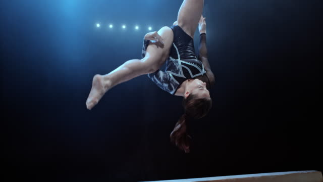 stockvideo's en b-roll-footage met speed ramp female gymnast performing a flip on the balance beam - gym