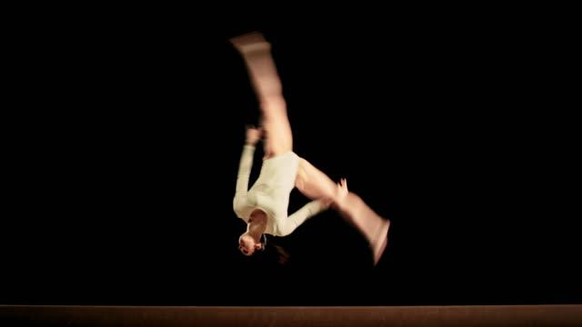 ld female gymnast performing on balance beam - cartwheel stock videos & royalty-free footage