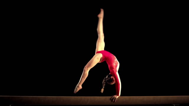 SLO MO Female gymnast performing on the balance beam