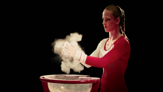 SLO MO Female gymnast removing excess chalk by clapping