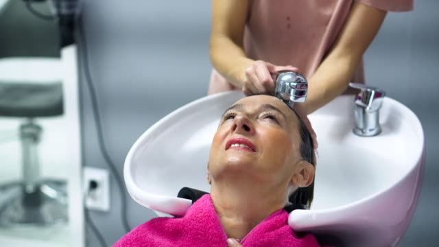 female hairdresser and senior woman in a hair salon - beauty spa stock videos & royalty-free footage