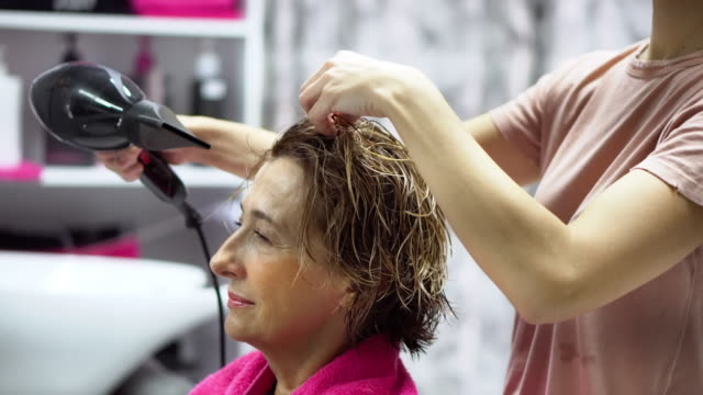 female hairdresser and senior woman in a hair salon - washing hair stock videos & royalty-free footage