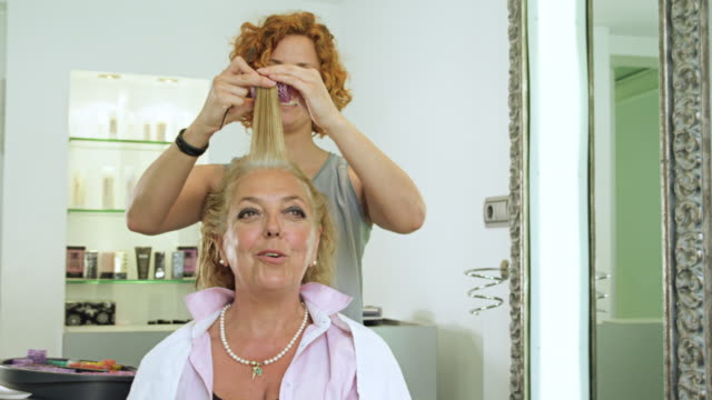 MS female hairdresser applying curlers to hair of mature female client, both chat and laugh
