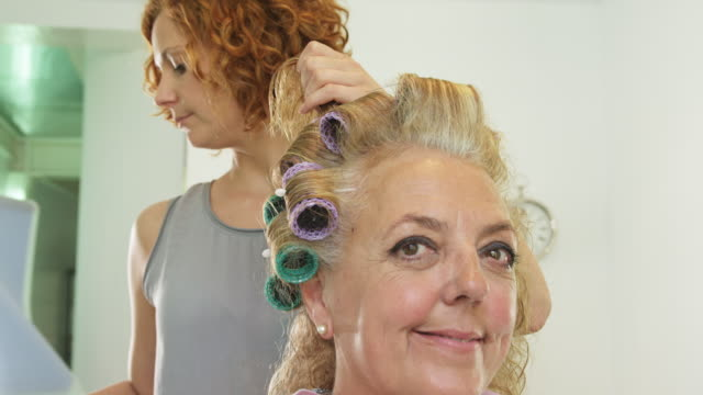 LA CU female hairdresser applying curlers to hair of mature female client