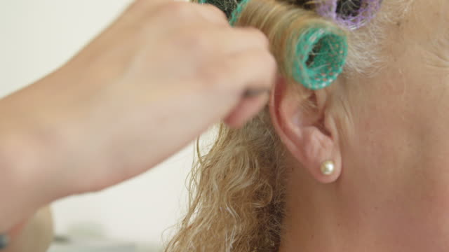 ECU female hairdresser applying hairspray and curlers to hair of mature female client