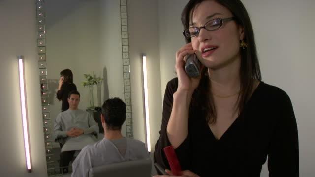 cu, tu, female hairstylist talking on phone in salon, client sitting in front of mirror, santa fe, new mexico, usa - sladdlös telefon bildbanksvideor och videomaterial från bakom kulisserna