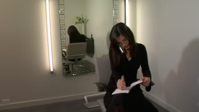 vídeos de stock e filmes b-roll de td, ms, female hairstylist talking on phone in salon, santa fe, new mexico, usa - telefone sem fio