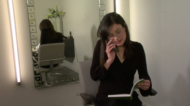 zi, cu, female hairstylist talking on phone in salon, santa fe, new mexico, usa - コードレスフォン点の映像素材/bロール