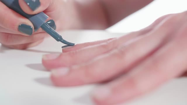 female hand applying dark grey nail polish - painting toenails stock videos & royalty-free footage