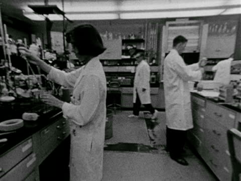 vídeos de stock, filmes e b-roll de female hand arranging test tubes in holder, female adding material to tube, dolly back female & male working in lab. intelligence: vs girl writing... - 1965