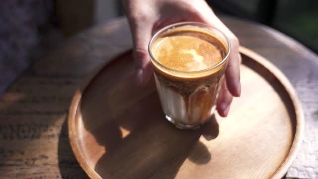 kvinnlig hand dricker varm kaffekopp på bordet med morgonsol. - stilleben bildbanksvideor och videomaterial från bakom kulisserna