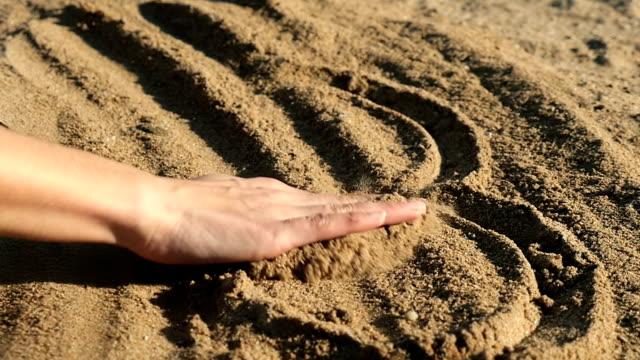 female hand erasing heart shape in sand - broken heart stock videos and b-roll footage
