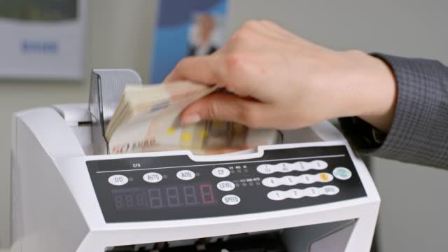 vídeos de stock, filmes e b-roll de feminino mão alimentação notas de cinquenta euros para o balcão de dinheiro e eles shuffle através dele - moeda da união europeia