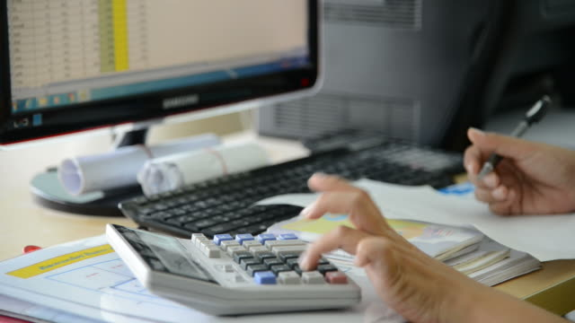 Female hand in Working Payroll workers. Calculation at office